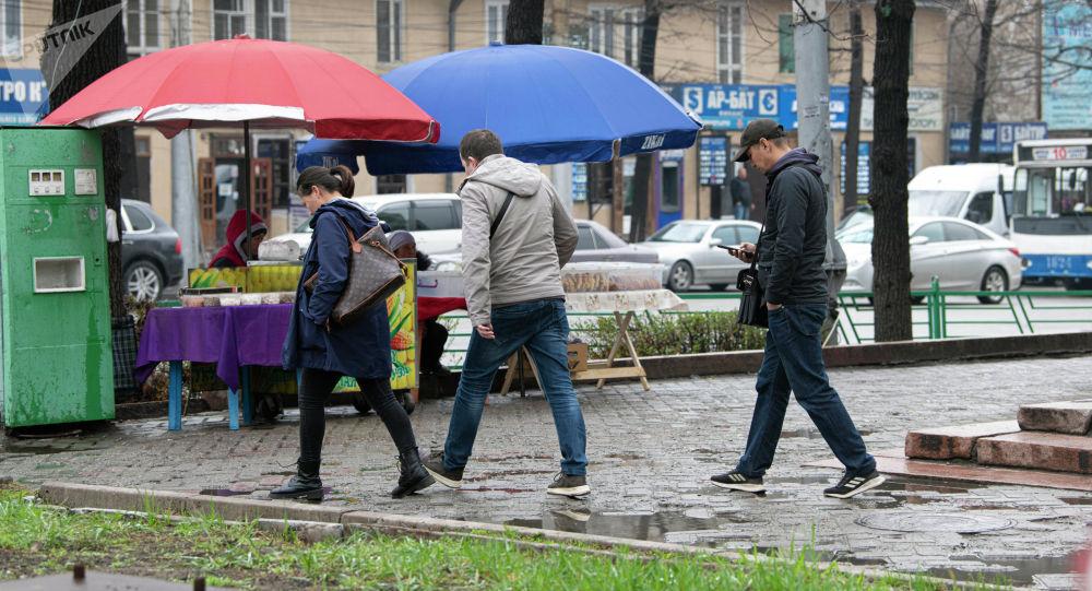 Люди идут по тротуару на одной из улиц Бишкека во время дождя. Архивное фото