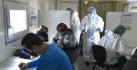 Люди заполняют анкеты перед вакцинацией от COVID-19 вакциной Спутник-V (Гам-КОВИД-Вак) в мобильном пункте в Краснодаре.