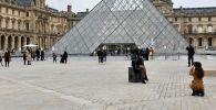 Люди в масках у входа в музей Лувр в Париже. Архивное фото