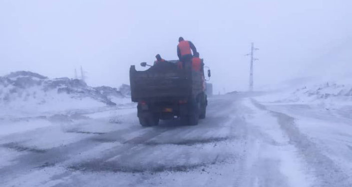 Дорожники подсыпают инертные материалы во время снегопада на участке автодороги Бишкек — Ош. 01 апреля 2021 года