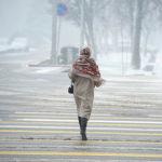 Девушка переходит дорогу во время апрельской снежной бури в Бишкеке