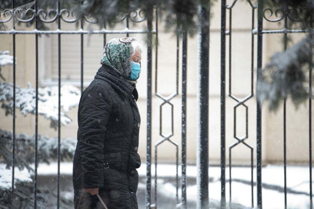 Женщина идет по улице во время апрельской снежной бури в Бишкеке