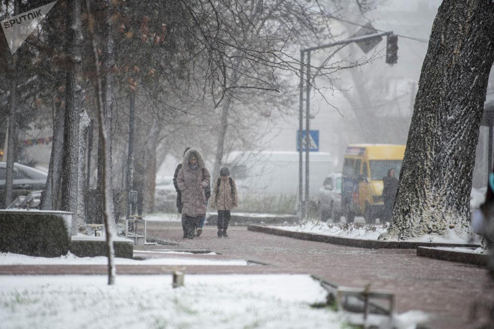 Люди идут по улице во время апрельской снежной бури в Бишкеке