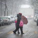 Женщина с ребенком идут по улице во время апрельской снежной бури в Бишкеке