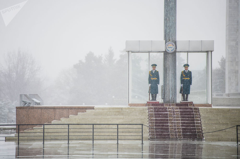 Солдаты национальной гвардии охраняют флагшток на площади Ала-Тоо во время апрельской снежной бури в Бишкеке