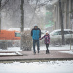 Мужчина с ребенком идут по улице во время апрельской снежной бури в Бишкеке