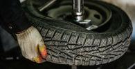 Работник меняет резину на колесе в шиномонтажной мастерской. Архивное фото