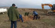 Захоронение найденных человеческих костей на берегу Токтогульского водохранилища