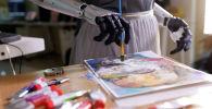 Робот-гуманоид София, разработанный Hanson Robotics, рисует на листе бумаги свой автопортрет в Гонконге