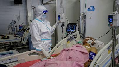 Медицинский работник проверяет монитор пациента с COVID-19. Архивное фото