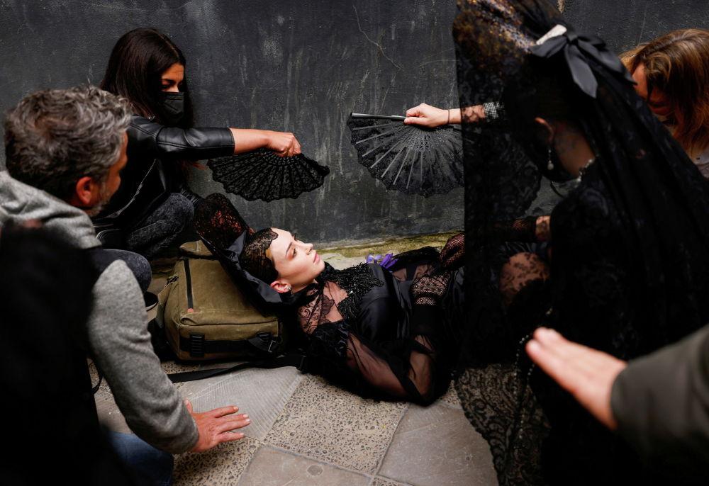 Испаниянын Севилья шаарында өткөрүлгөн улуттук кийимдердин салттуу мода көргөзмөсүнүн алдында башы айланып кулаган моделге аялдар жардам берип жатышат