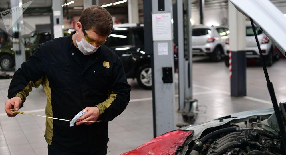Сотрудник автоцентра проверяет уровень масла в автомобиле. Архивное фото