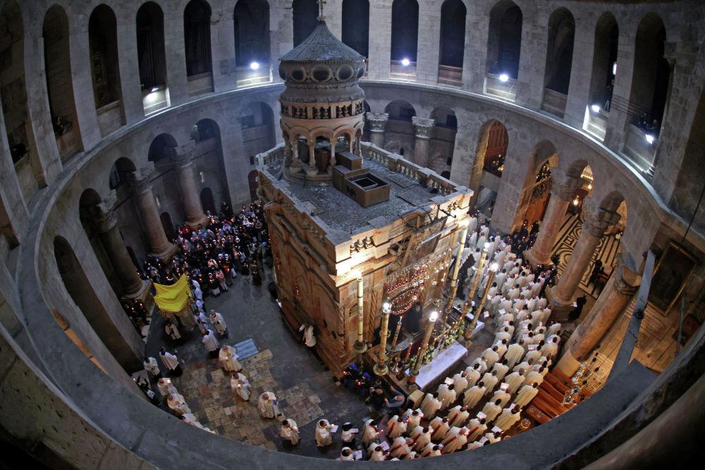 Сыйынуучулар жана монахтар бейшемби күнү Иерусалимдеги Ыйык сыйынуу чиркөөсүндө Иисус Христостун сөөгү коюлган Кувуклиянын айланасында жүрүш жасашты