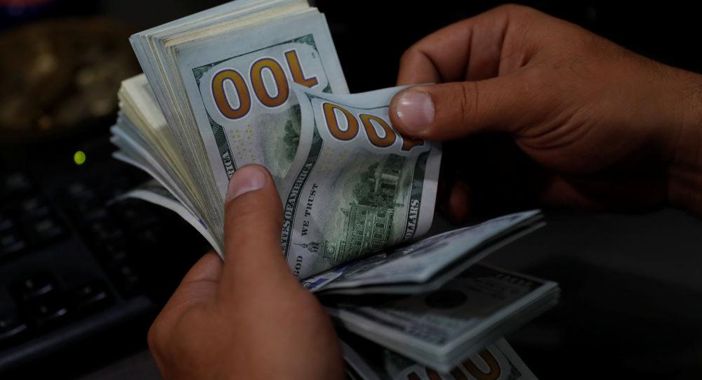 Киши долларларды санап жатат. Архив