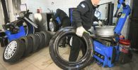 Сотрудники автоцентра производят шиномонтаж колес. Архивное фото