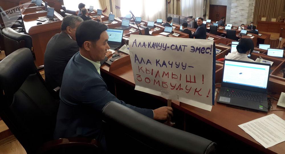 Жогорку Кеңештин депутаты Эмил Токтошев парламенттин жыйынына ала качууну жектеген плакат көтөрүп келди