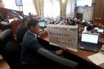 Депутат Жогорку Кенеша Эмиль Токтошев с плакатом против кражи невест на заседании
