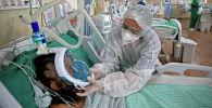 Медициналык кызматкер COVID-19 менен ооруган адамга жардам берип жатат. Архив