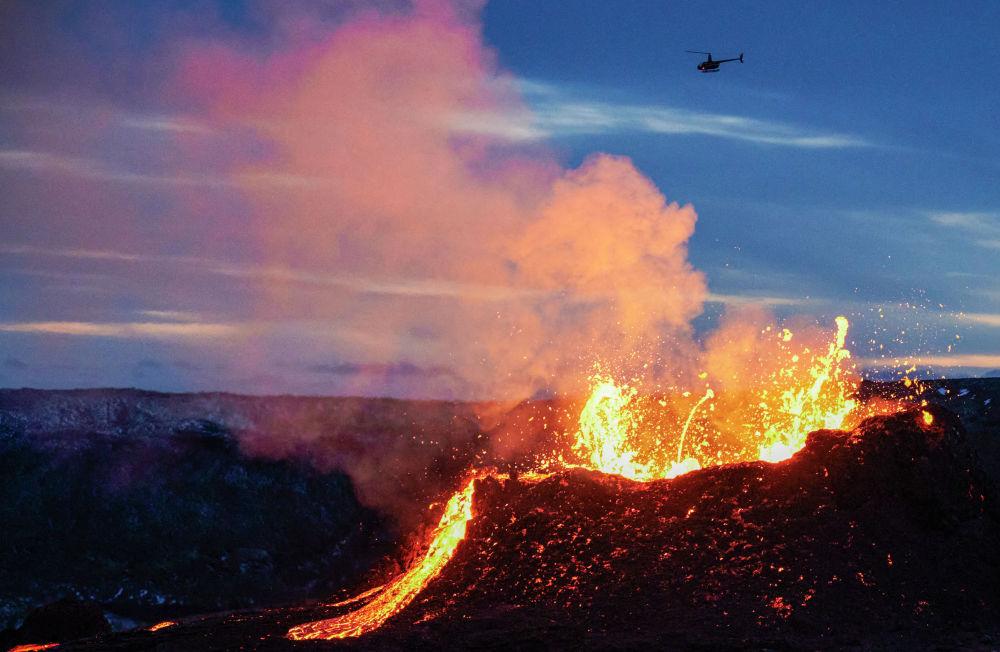 Вертолет пролетает над извергающимся вулканом Фаградальсфьядль в Исландии.