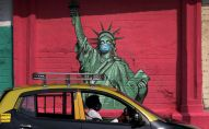 Такси проезжает мимо фрески Статуи Свободы с маской на лице. Архивное фото