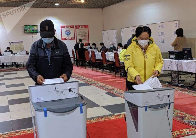 Люди голосуют на избирательном участке № 1 053 в Чон-Арыке во время выборов в местные кенеши и референдум по проекту новой Конституции в Кыргызстане