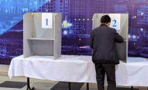 Мужчина голосует на избирательном участке № 1 053 в Чон-Арыке во время выборов в местные кенеши и референдум по проекту новой Конституции в Кыргызстане