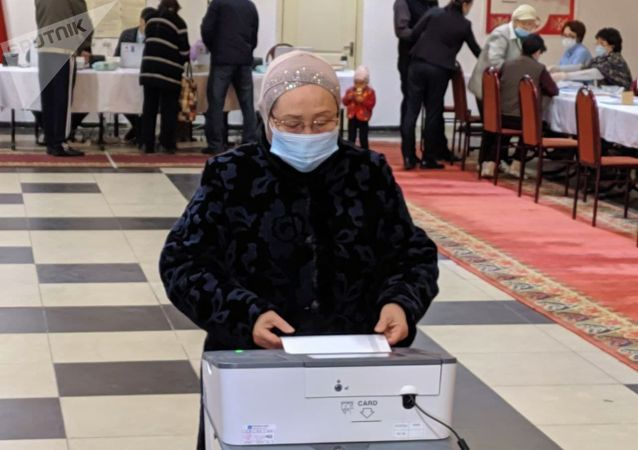 Женщина голосует на избирательном участке № 1 053 в Чон-Арыке во время выборов в местные кенеши и референдум по проекту новой Конституции в Кыргызстане