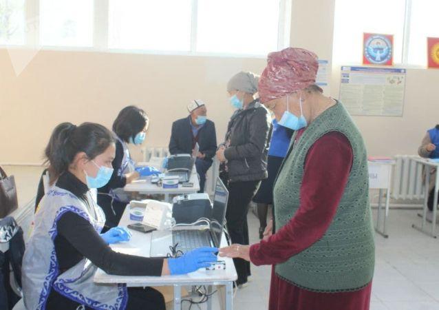 Избиратели проходят процедуру идентификации в одном из участков Баткенской области во время выборов в местные кенеши и референдум по проекту новой Конституции в Кыргызстане