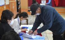 Мужчина голосует на избирательном участке № 1032 в городе Бишкек, во время выборов в местные кенеши и референдум по проекту новой Конституции в Кыргызстане