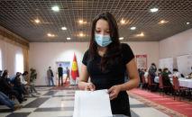 Девушка голосует на избирательном участке № 1 053 в селе Чон-Арык во время выборов в местные кенеши и референдум по проекту новой Конституции в Кыргызстане
