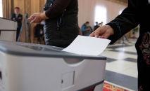 Люди голосуют на избирательном участке