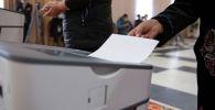 Женщина голосует на избирательном участке № 1 053 в селе Чон-Арык во время выборов в местные кенеши и референдум по проекту новой Конституции в Кыргызстане