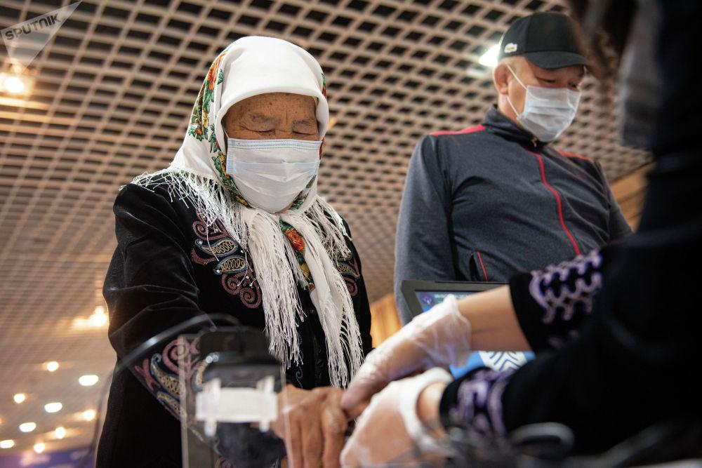 Оператор проверяет биометрические данные женщины на избирательном участке №1053 в селе Чон-Арык во время выборов в местные кенеши и референдум по проекту новой Конституции в Ленинском районе
