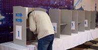 Мужчина голосует на избирательном участке №1053 в селе Чон-Арык во время выборов в местные кенеши и референдум по проекту новой Конституции в Кыргызстане