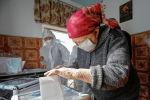 Женщина опускает бюллетень в урну во время досрочного голосования на выборах в местные кенеши и референдум по проекту новой Конституции в Кыргызстане