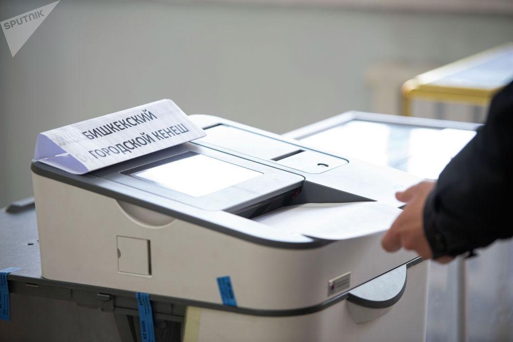 Мужчина голосует на избирательном участке №1219 в Бишкеке во время выборов в местные кенеши и референдум по проекту новой Конституции.