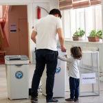 Мужчина с ребенком голосуют на избирательном участке №1219 в Бишкеке во время выборов в местные кенеши и референдум по проекту новой Конституции.