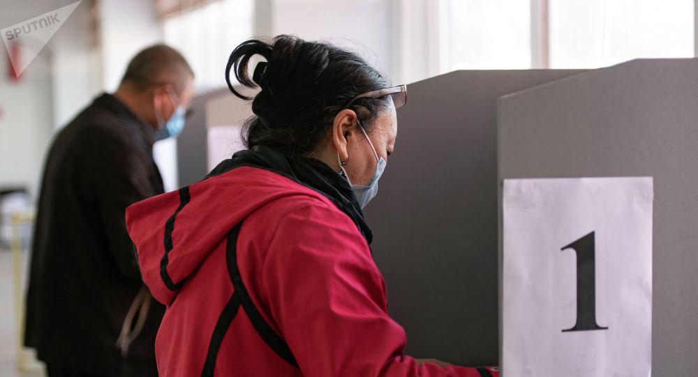 Женщина голосует на избирательном участке