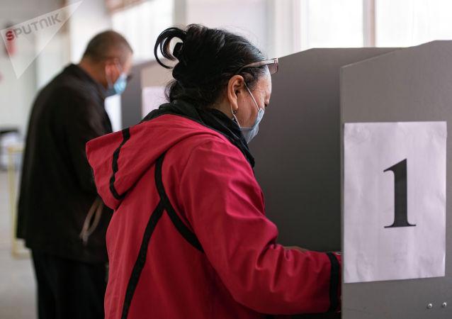 Женщина голосует на избирательном участке №1219 в Бишкеке во время выборов в местные кенеши и референдум по проекту новой Конституции.