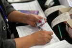 Оператор устанавливает личность на избирательном участке №1219 в Бишкеке во время выборов в местные кенеши и референдум по проекту новой Конституции.
