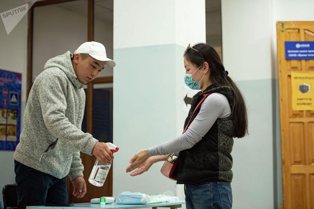 Девушка обрабатывает руки дезинфицирующим средством на избирательном участке №1219 в Бишкеке во время выборов в местные кенеши и референдум по проекту новой Конституции.