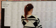 Бишкектеги участкасында кыз шайлоочулардын тизмесин карап жатат. Архив