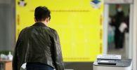 Девушка голосует на избирательном участке в Бишкеке