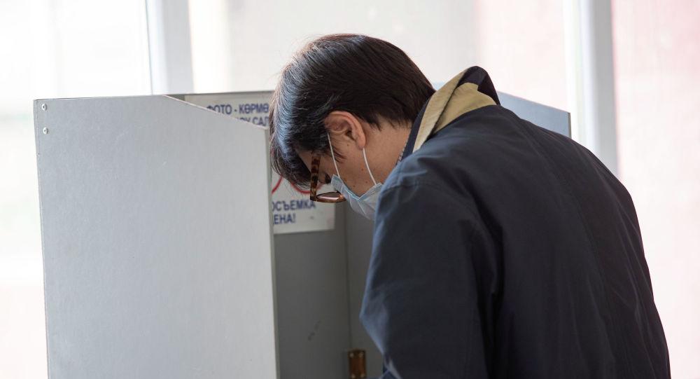 Мужчина голосует на избирательном участке в Бишкеке