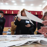 Сотрудники избирательной комиссии во время подсчета голосов на одном из избирательных участков в Бишкеке после окончания голосования на выборах в местные кенеши и референдум по проекту новой Конституции в Кыргызстане