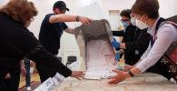 Сотрудники избирательной комиссии во время подсчета голосов на одном из избирательных участков в Бишкеке