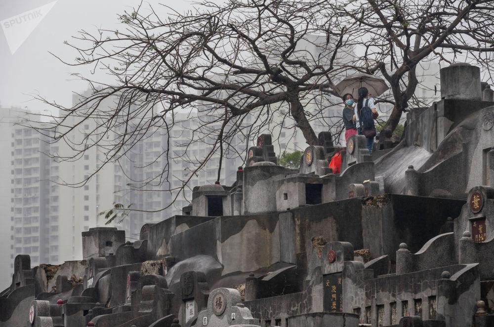 Посетители кладбища во время праздника Цинмин в Гонконге.