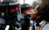 Демонстрант возле сотрудников полиции во время акции протеста в Миннесоте (США)