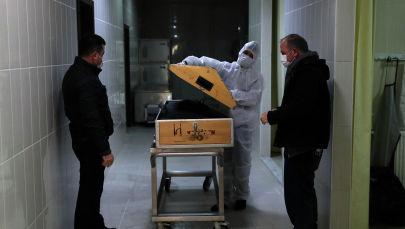 Муниципальные работники и родственники покойного стоят у гроба. Архивное фото