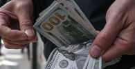 Сотрудник бюро обмен валюты пересчитывает доллары США. Архивное фото